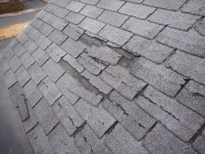 Damaged asphalt shingles in need of replacing